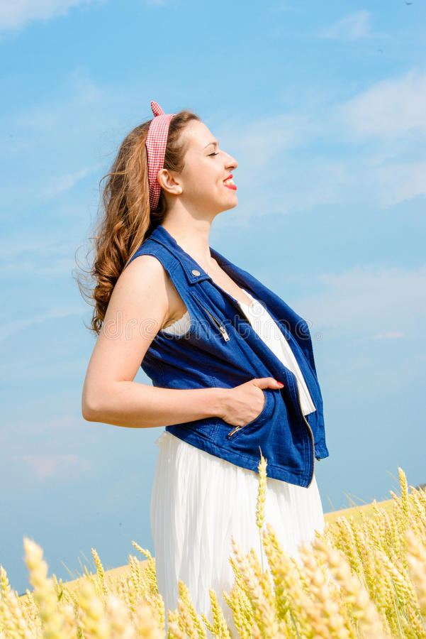 A beautiful young woman on a wheat field royalty free stock image