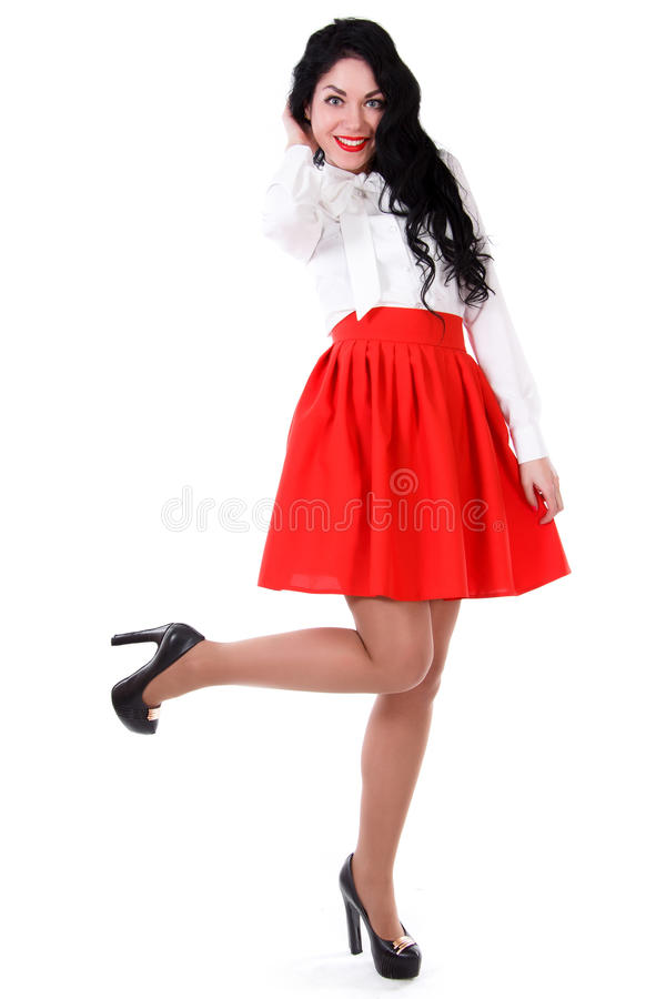 Beautiful young woman in a white blouse and a red skirt stock image