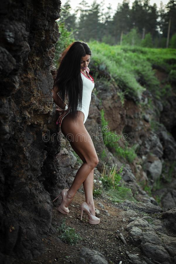 Beautiful young woman in white bodysuit with heels posing on stone background. Outdoor. Green.  stock images