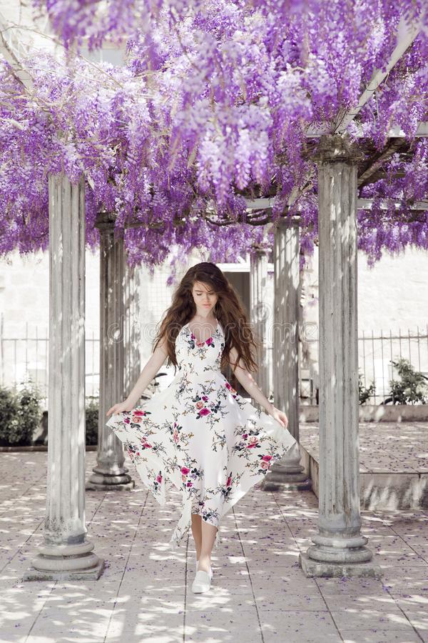 Beautiful young woman in white flying dress over wisteria tunnel. Arch. Attractive brunette girl with long healthy hair in spring purple park, natural lilac stock image