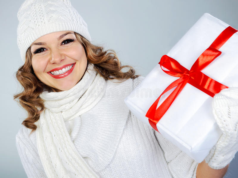 Beautiful young woman in white hat holding Christmas present stock photos
