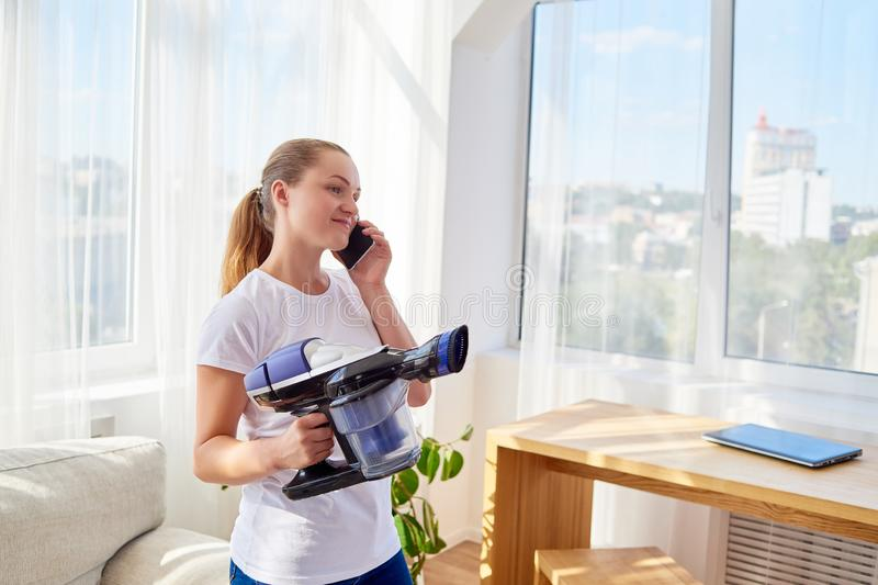 Beautiful young woman in white shirt holding vacuum cleaner and talking on cellphone, copy space. Housework, spring-cleanig. royalty free stock photos