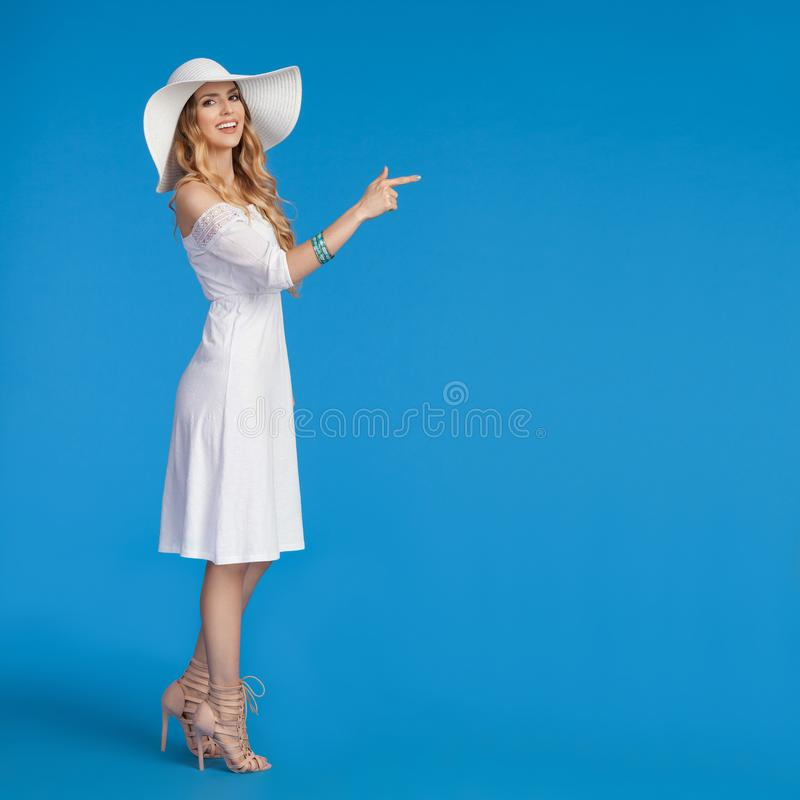 Young Woman In White Summer Dress And Sun Hat Is Pointing. Beautiful young woman in white summer dress, high heels and sun hat is standing, pointing and looking stock images