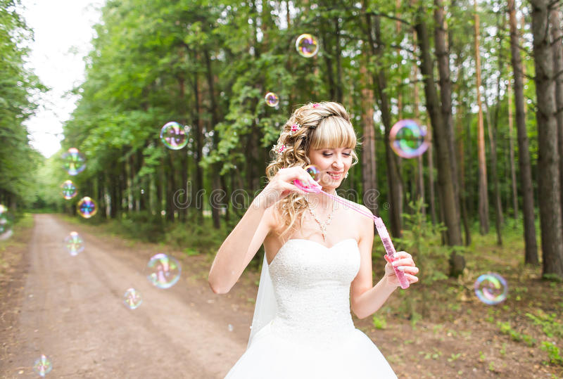 Beautiful young woman with white wedding dress blowing bubble outdoors royalty free stock image