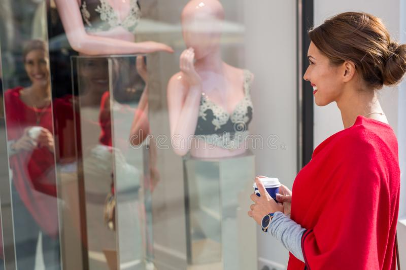 Beautiful young woman window shopping for lingerie stock photography