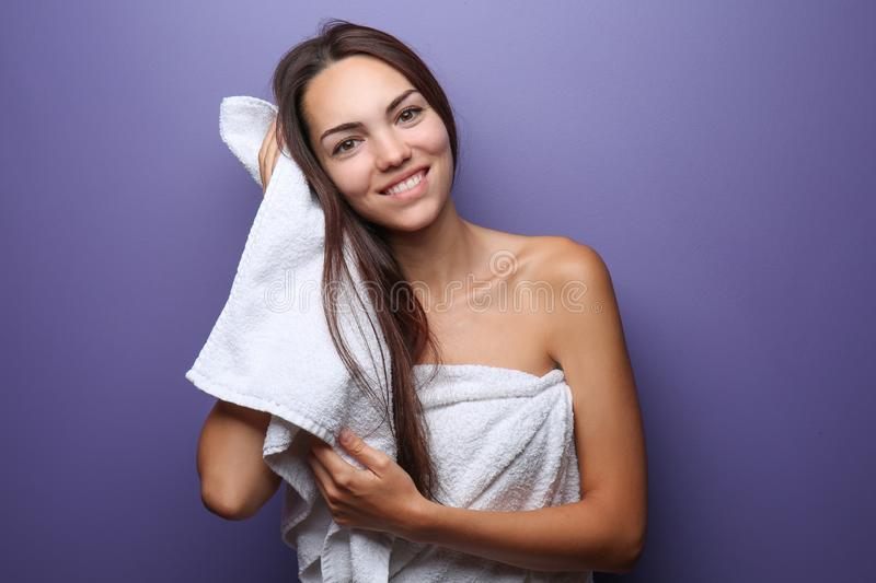 Beautiful young woman wiping hair with towel on color background stock photo