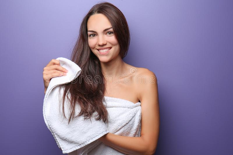 Beautiful young woman wiping hair with towel on color background royalty free stock image