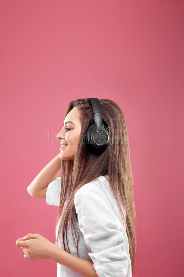 Beautiful young woman in wireless headphones listening to music and dancing on pink background. Girl uses wireless earphones royalty free stock photos