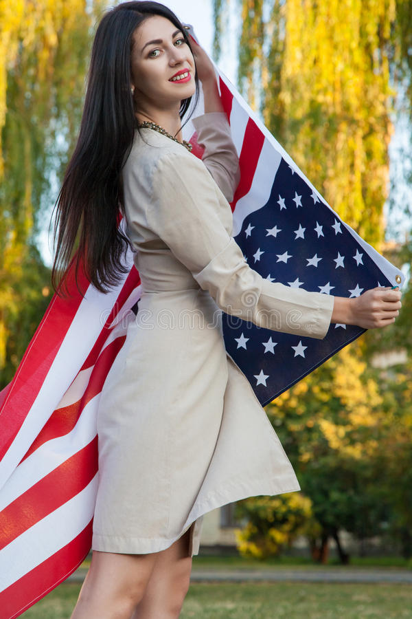 Free Beautiful Young Woman With Classic Dress Holding American Flag In The Park. Fashion Model Holding Us Smiling And Looking At Camera Stock Photography - 62417502
