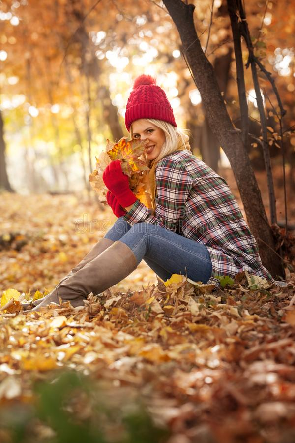 Beautiful young woman with woolen hat fun with fall leaves stock image