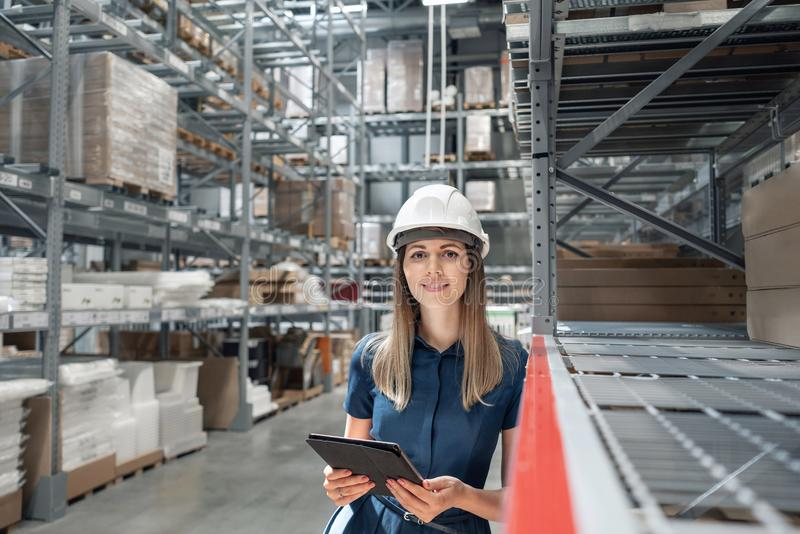 Beautiful young woman worker of furniture store in shopping center. Girl looking for goods with a tablet is checking royalty free stock photos