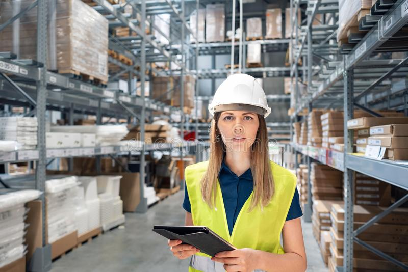 Beautiful young woman worker of furniture store in shopping center. Girl looking for goods with a tablet is checking royalty free stock images