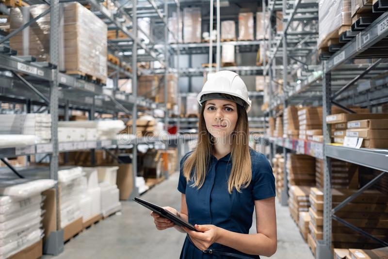 Beautiful young woman worker of furniture store in shopping center. Girl looking for goods with a tablet is checking stock image