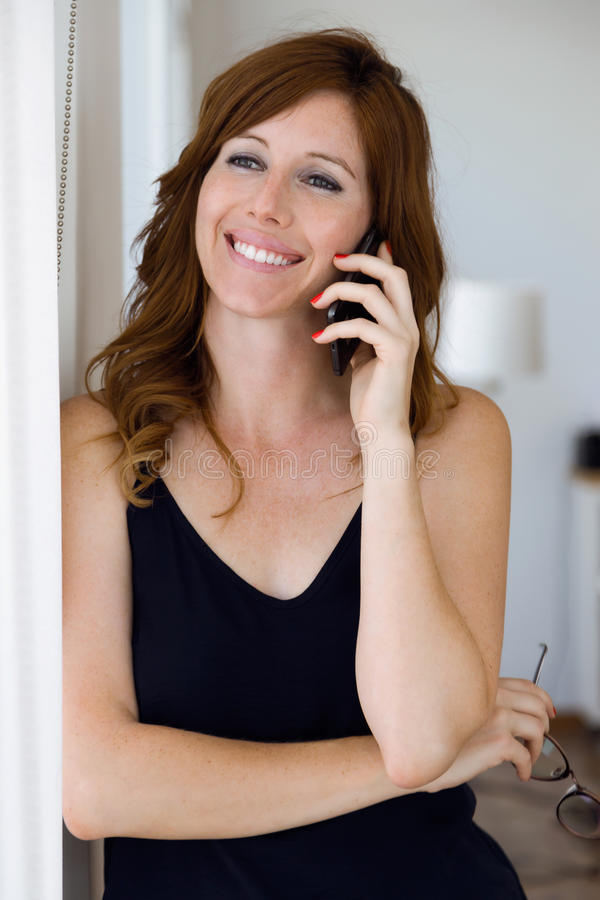 Beautiful young woman working with her mobile phone at home. royalty free stock photo