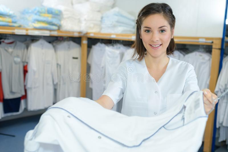 Beautiful young woman working at laundry royalty free stock images