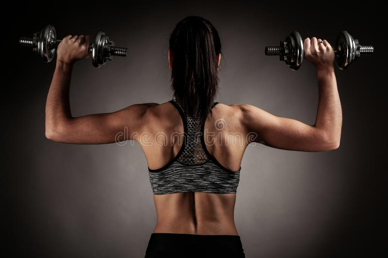 Beautiful young woman workout with dumbbell over gray background in fitness gym club royalty free stock image