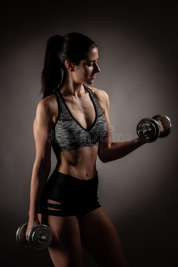 Beautiful young woman workout with dumbbell over gray background in fitness gym club stock photography