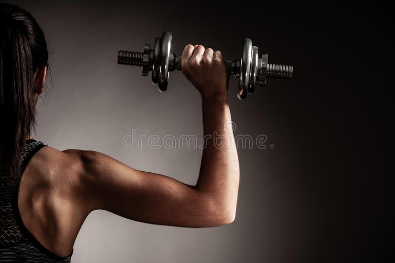 Beautiful young woman workout with dumbbell over gray background in fitness gym club royalty free stock photography