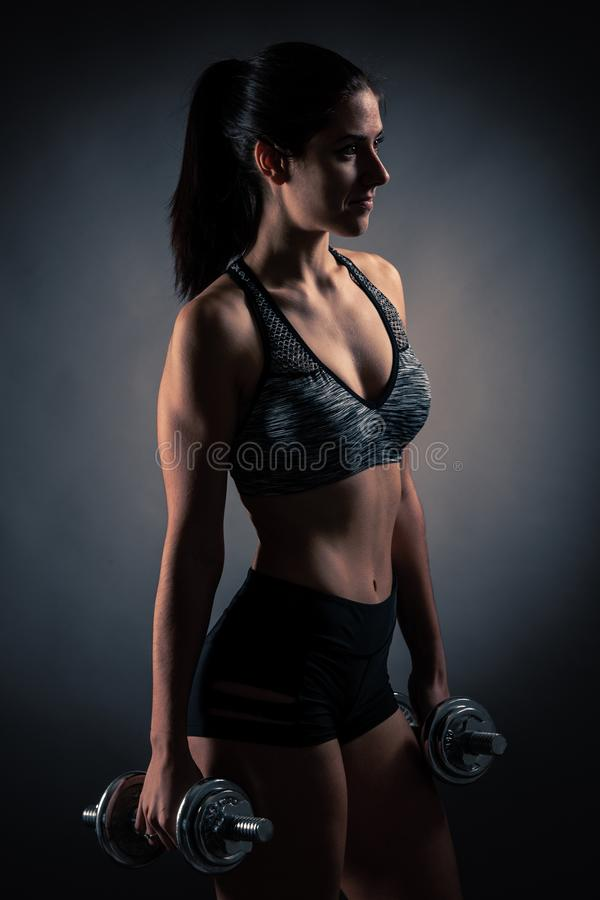 Beautiful young woman workout with dumbbell over gray background in fitness gym club royalty free stock photos