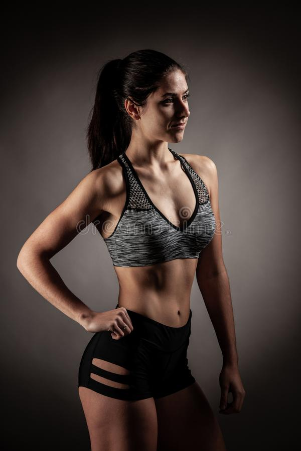 Beautiful young woman workout with dumbbell over gray background in fitness gym club stock photo