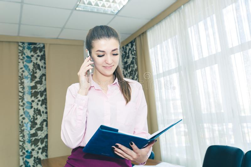Beautiful young woman at workplace in office with phone and Notepad. Business concept. Planning of the working day royalty free stock photos