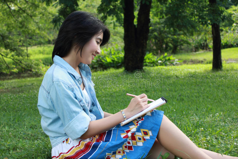 Download Beautiful Young Woman Writing Outdoors In A Park Stock Photo - Image of hair, cute: 16112590