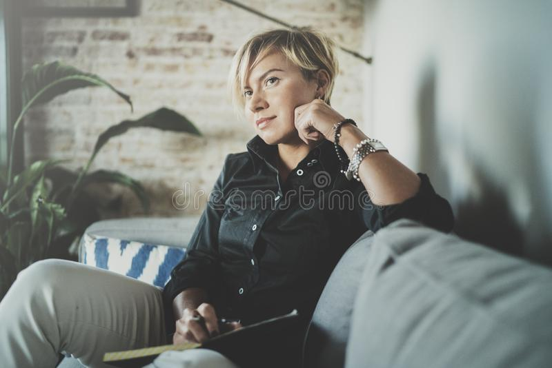 Beautiful young woman writing something in note pad while sitting on armchair at living room.Charming female studying stock image