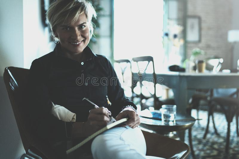 Beautiful young woman writing something in note pad while sitting on armchair at living room.Charming female studying. Doing homework at home.Horizontal.Blurred stock photo