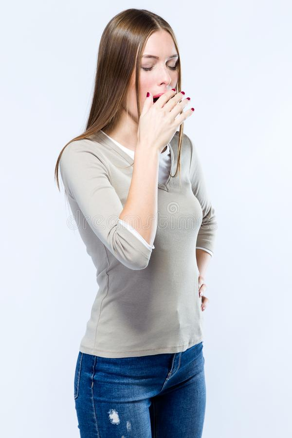 Beautiful young woman yawning over white background. stock photography