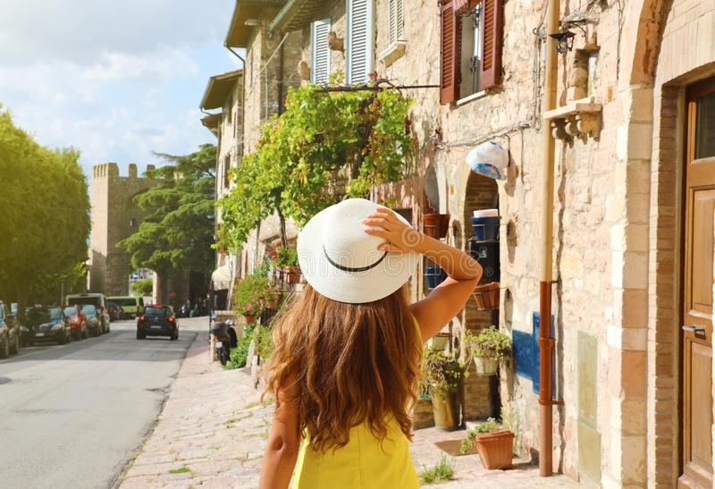 Beautiful young woman with yellow dress and hat walking in typical Assisi street, Italy. Rear view of happy cheerful girl visiting stock photos