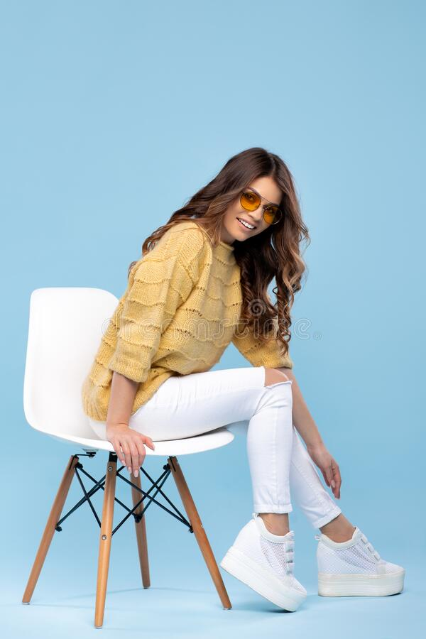Beautiful young woman in yellow sweater posing on blue background. Pretty girl in yellow glasses. royalty free stock images