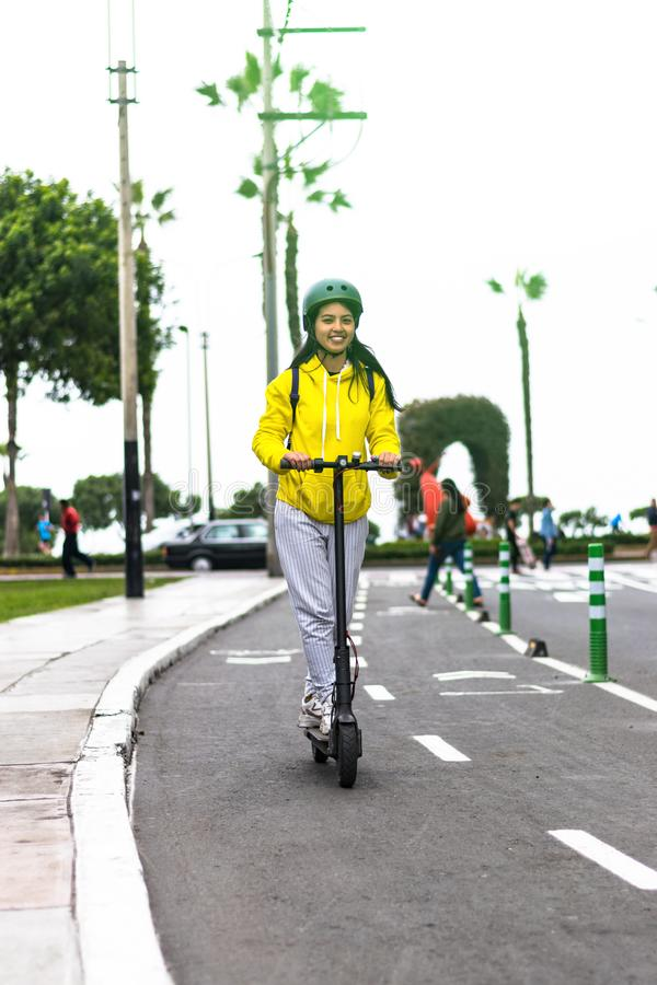 Beautiful young woman with a yellow sweater riding an electric scooter. stock images