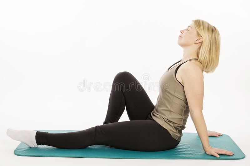 Beautiful young woman on a yoga mat relaxes royalty free stock images