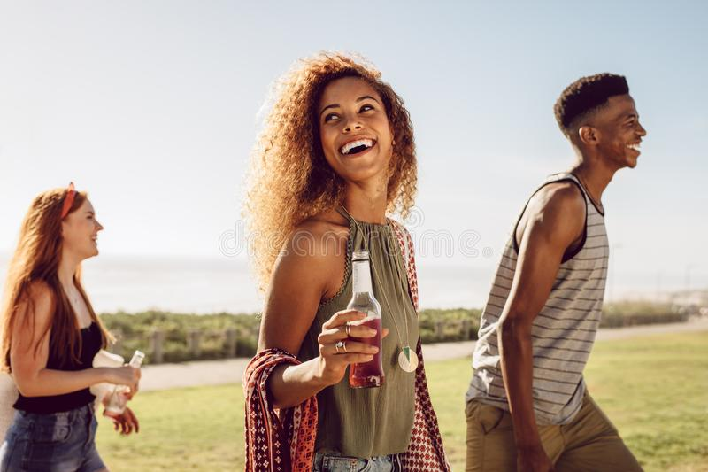 Woman hanging out with friends. Beautiful young women with beer walking with friends outdoors on a summer day. Female hanging out with friends outdoors royalty free stock photography