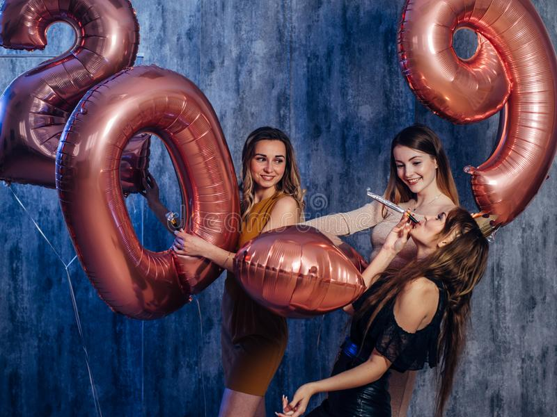Beautiful young women celebrating playing holding balloons. New year, Christmas, Xmas.  royalty free stock photography