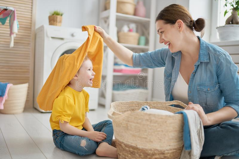 Family doing laundry. Beautiful young women and child girl little helper are having fun and smiling while doing laundry at home royalty free stock image