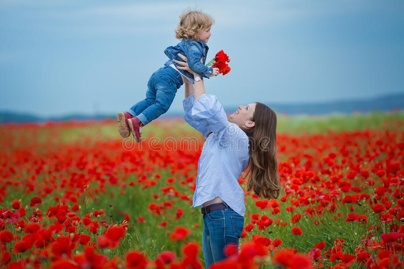Beautiful young woman with child girl in poppy field. happy family having fun in nature. outdoor portrait in poppies. mother with royalty free stock image