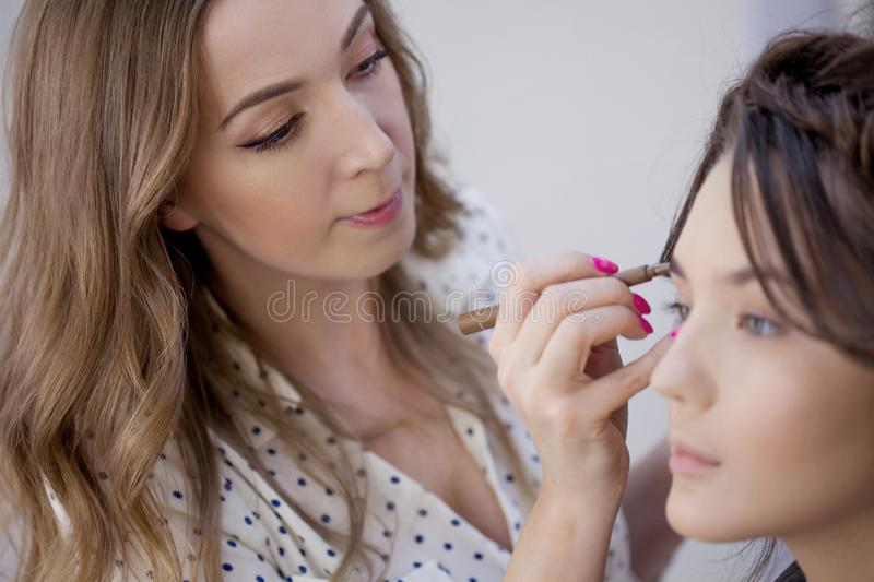 Beautiful young woman doing makeup at a professional makeup artist. Correction and colouring of eyebrows royalty free stock image