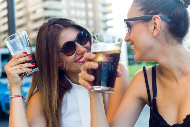 Beautiful young women drinking refreshment in the street. Portrait of beautiful young women drinking refreshment in the street stock images