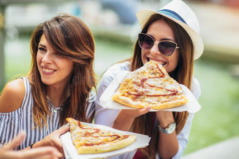 Beautiful young women eating pizza after shopping, having fun together stock images