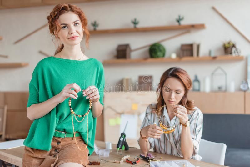 Beautiful young women with handmade accessories. Beautiful young woman with handmade accessories in workshop stock photography