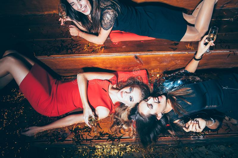 Beautiful young women having fun on crazy party lying on the flo. Or. New year, Birthday, Holiday Event Concept stock photo