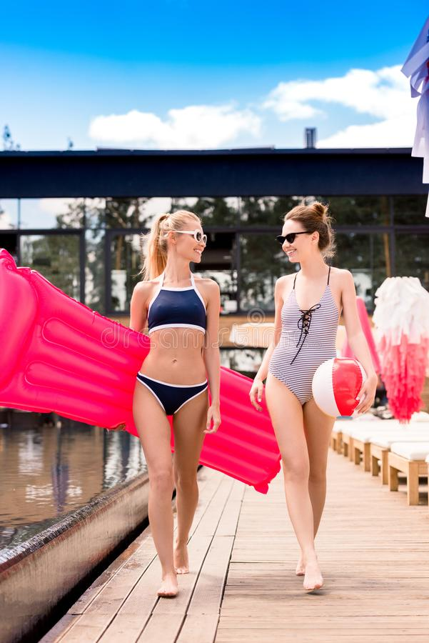 beautiful young women with inflatable mattress and beach ball walking stock photography