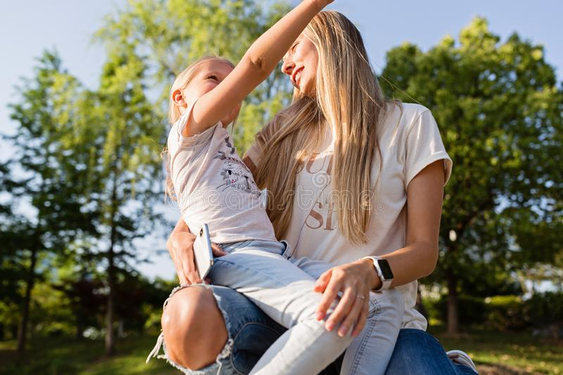 Beautiful young mother and daughter with blonde hair embracing outdoor. Stylish girls making walking in the park. Family concept stock images