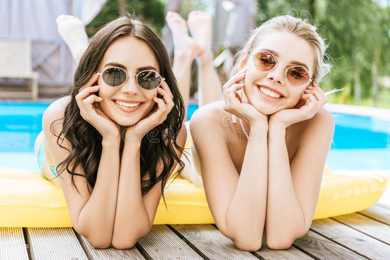Beautiful young women lying on inflatable mattress and smiling at camera. At poolside stock photos