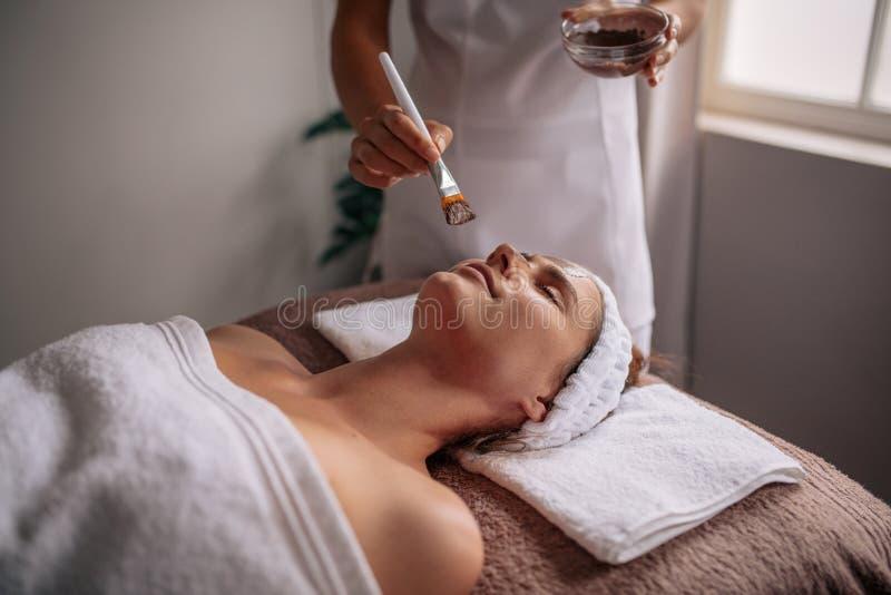 Woman getting facial mask at spa salon royalty free stock image