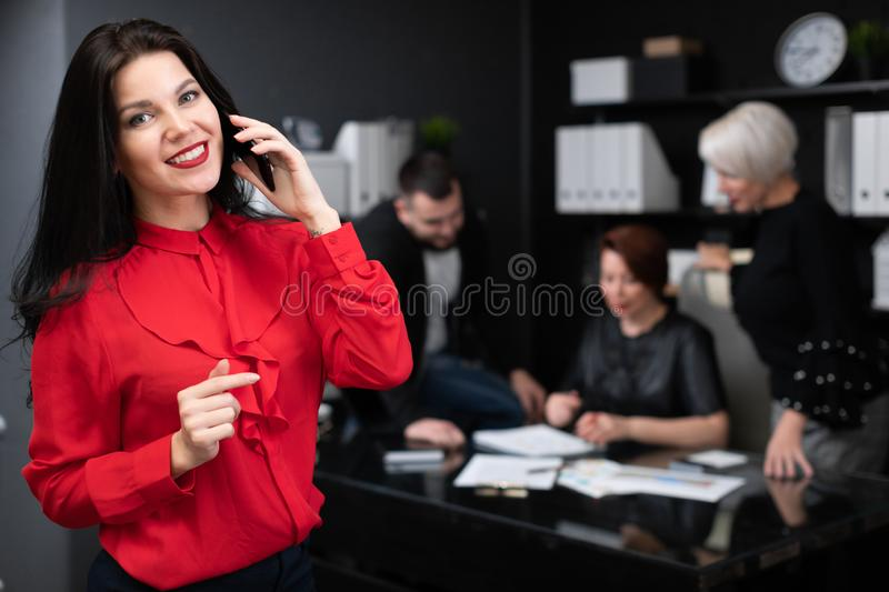 Businesswoman talking on phone on background of Office workers discussing project stock images
