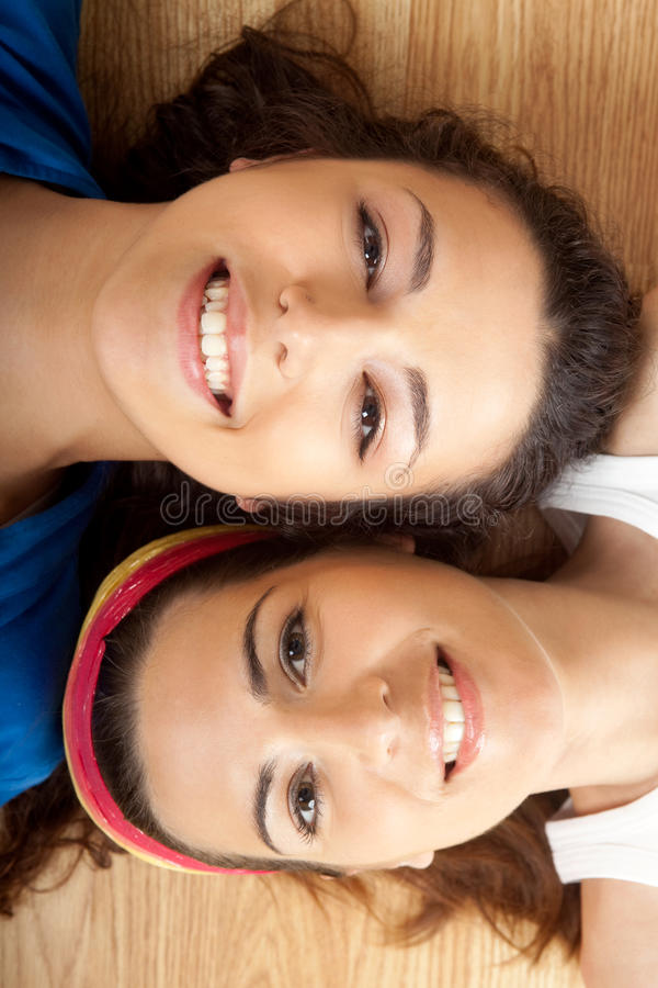 Beautiful young women's. Portraits of two beautiful young women on the floor royalty free stock photography