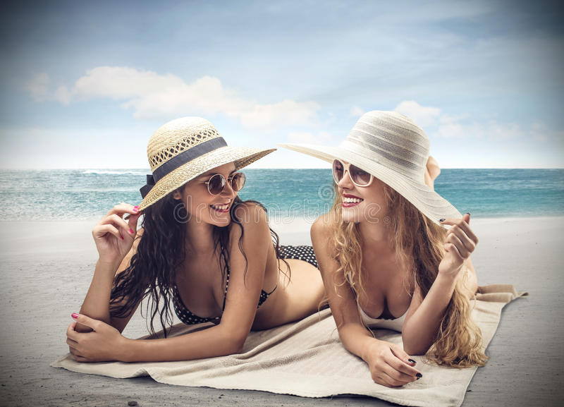 Beautiful young women at the sea side. Beautiful young women sun bathing at the sea side royalty free stock images