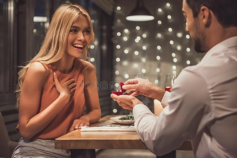 Man proposing in restaurant. Beautiful young women is smiling while her boyfriend is holding an engagement ring and proposing to her in a restaurant stock image